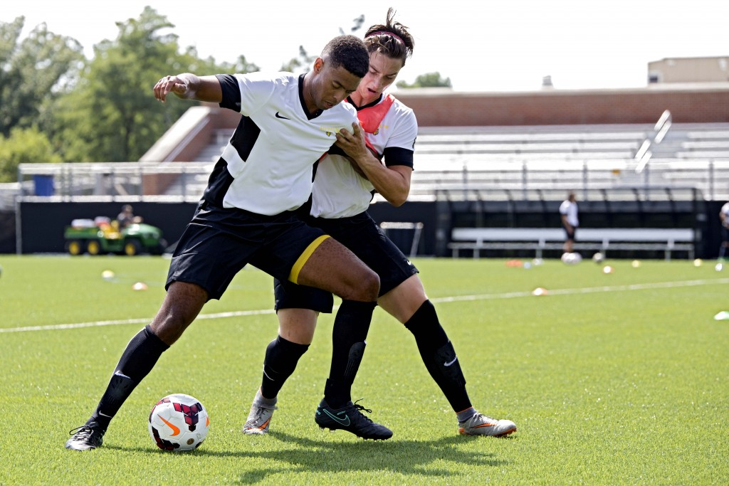 Senior midfielder E.J. Moore (left) dribbles past his teammate and fellow senior, Jay Wheeler (right), during practice Thusday. The Tiger's first game is September 1 at 7:00 p.m .. SAM CARAVANA / THE DEPAUW