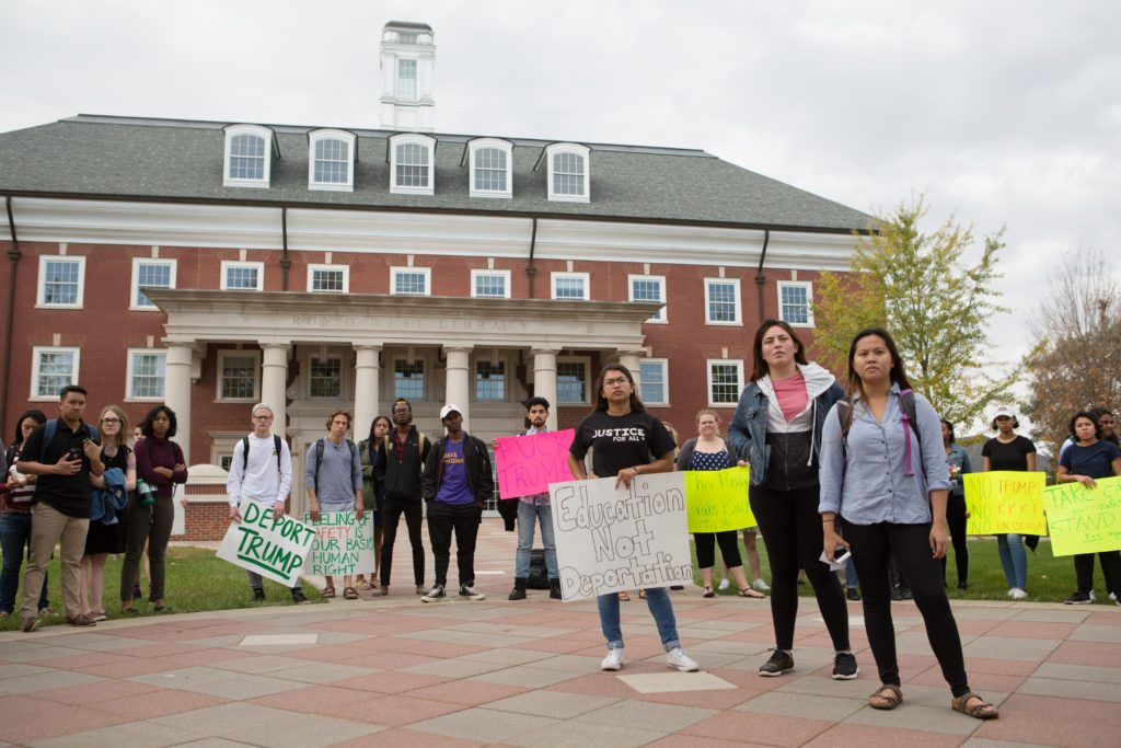 Junior Maggie Rocha and seniors Jackie Rueda and Nancy Huynh (left to right) stand in the middle of a circle of protesters. The trio led the demonstration and demanded a meeting with the administration by Nov. 30 to talk about making DePauw a sanctuary campus. SAM CARAVANA / THE DEPAUW