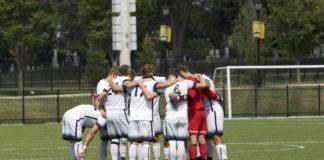The Men's Soccer team huddles up before heading into overtime. REID COOPER