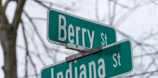 Green street signs at the corner of Berry St and Indiana St